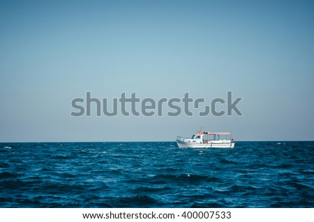 Lonely tourist boat in the Black Sea without people. Blue sky and dark water. - stock photo