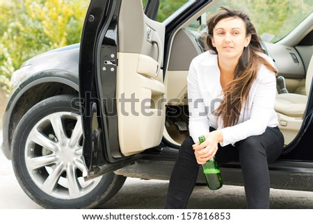 Lonely unhappy drunk woman sitting at the roadside in her parked car drinking alcohol directly from the bottle - stock photo