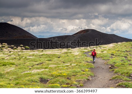 Lonely unrecognizable Hiker dressed in in red walks along a path on Mount Etna in Sicily, heading to a black volcano crater. - stock photo