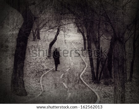 Lonely walk, rite of passage concept, metaphorical image edited in the antique (vintage) style. - stock photo
