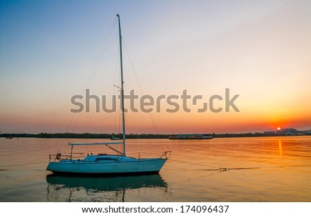 Lonely white sailboat before sunset - stock photo