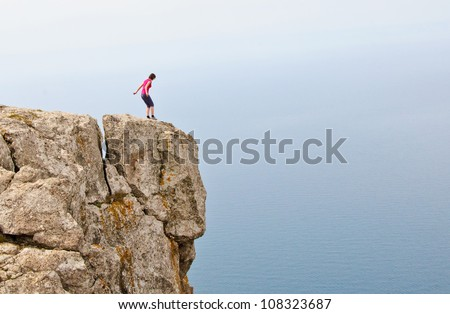 Lonely woman standing on the edge of the cliff near sea - stock photo