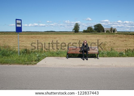 lonely woman waiting for a bus in rural area - stock photo