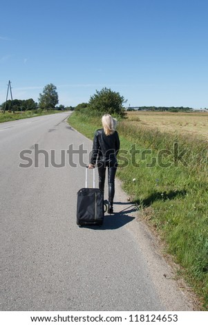 lonely woman with suitcase go along rural roadside - stock photo