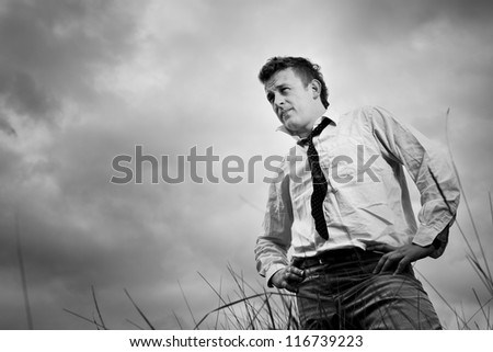 Lonely young man is a little concerned about, he  standing the meadow. In the background, overcast, photo black and white. - stock photo
