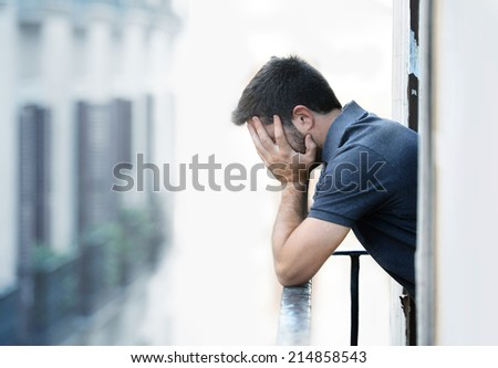 Lonely young man outside at house balcony looking depressed, destroyed, sad and suffering emotional crisis and grief in work and personal life problem on an urban background  - stock photo