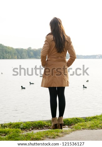 lonely young woman on lake, rear view - stock photo