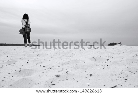 Lonely young woman on the beach, warm's eye view (black and white) - stock photo