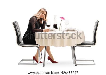 Lonely young woman sitting at a restaurant table and drinking wine isolated on white background - stock photo