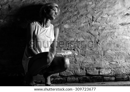 Lonely young woman sitting on the street, looking severely depressed. Black and white. - stock photo