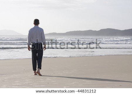 Lonesome businessman walking barefoot on a beach - stock photo