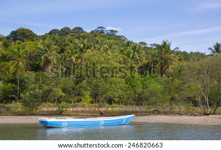Lonesome fishing boat in the amazon of brazil: Rain forest near Salvador in the Bahia de Todos. Landscape with a traditional handmade boat of wood. - stock photo