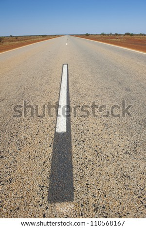 Long and lonely stretch of road in outback Australia leading towards horizon, with blue sky as background and copy space. - stock photo