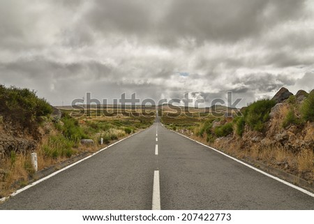 Long and straight endless road goes in to the horizon on the plateau Paul da Serra of Madeira. The sky is very cloudy, as if a storm is coming up. - stock photo