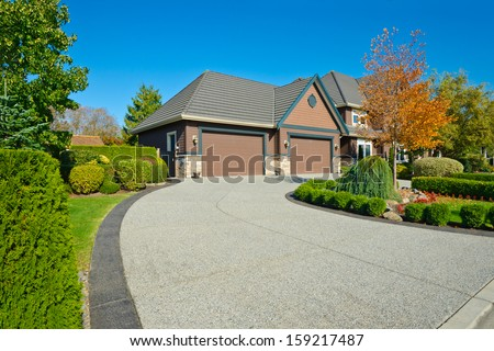 Long and wide nicely paved driveway to two double doors garage in the suburbs of Vancouver, Canada. - stock photo