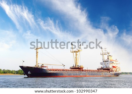 Long barge over dramatic blue sky - stock photo