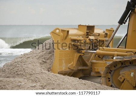 LONG BEACH ISLAND,NJ-NOVEMBER 3:A bulldozer pushes sand back up to the dunes after it was lost from the tidal surge caused by Hurricane SandyNov 3 2012, Long Beach Island, NJ - stock photo