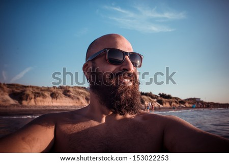 long bearded man in the beach with sunglasses in summertime - stock photo