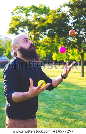 long bearded millennial bald man juggling with balls at the park in a spring day, playful positive concept - stock photo