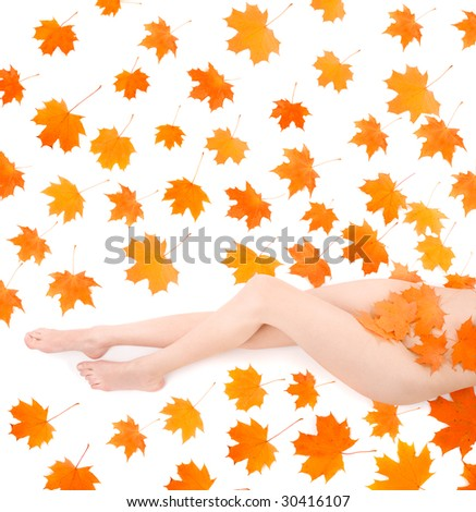 Long beautiful legs of nudity woman covering by maple leafs over white - stock photo