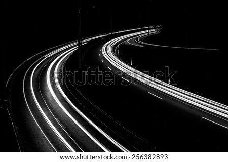 long black and white exposure of a highway in the evening. abstract picture with curved lines.  - stock photo