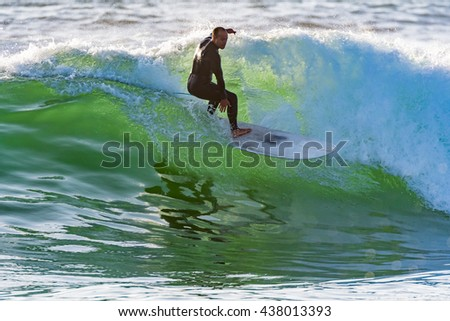 Long boarder surfing the waves at sunset in Portugal. - stock photo