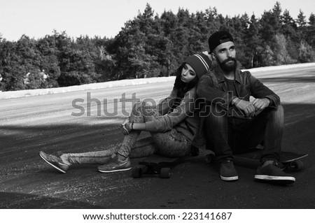 long boarders couple on a spot sitting on skateboards - stock photo