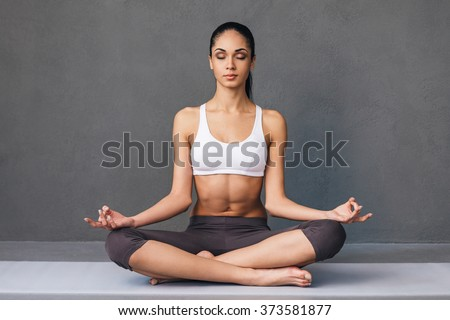Long breath in. Beautiful young African woman in sportswear practicing yoga while sitting in lotus position against grey background - stock photo