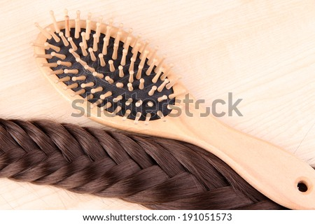 Long brown hair with hairbrush on wooden background - stock photo