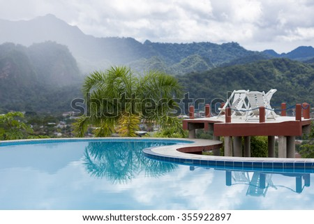 Long chairs standing by the swimming pool with tropical mountains in the background in Rurrenabaque, the gateway to the Bolivian Amazon rain forest. Bolivia 2015 - stock photo
