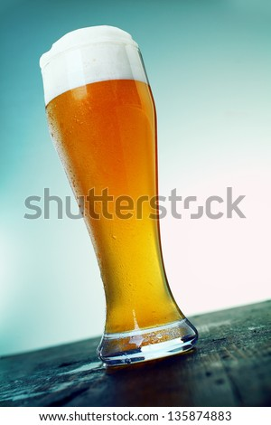 Long cold pint of beer in an elegant glass with a good head of froth standing on an old wooden counter of a bar or club, low angle view. Look at my portfolio for whole series of cocktails. - stock photo