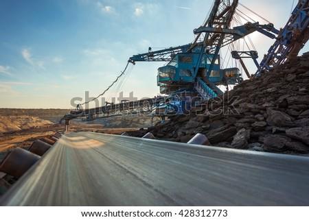 Long conveyor belt transporting ore - stock photo