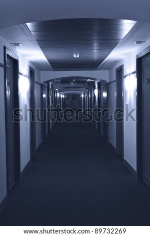 Long corridor in modern hotel. Blue toning - stock photo