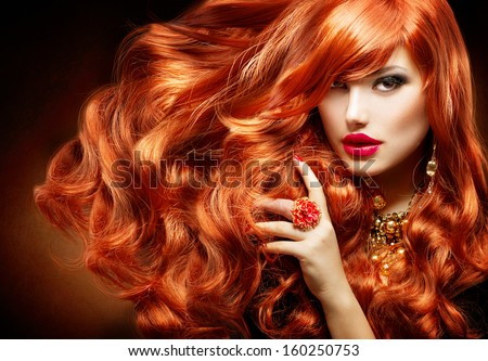 Long Curly Red Hair. Fashion Woman Portrait. Beauty Model Girl with Luxurious Hair, Make up and Accessories. Hairstyle. Wavy Hair Extensions Concept. Holiday Makeup. Smoky eyes and Red lipstick - stock photo
