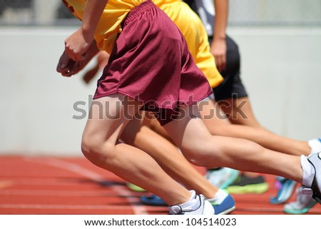 Long distance runners captured just after the start of a 1500 meter track and field race event. - stock photo
