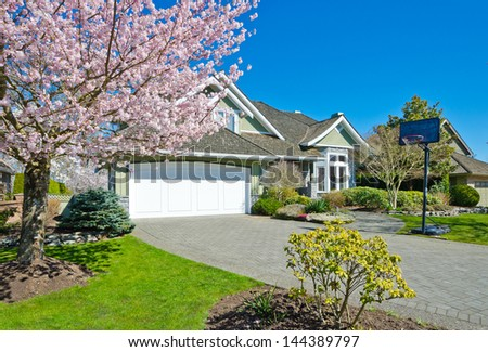 Long driveway to the double garage doors and nicely trimmed and landscaped front yard at cherry blossom time in the suburbs of Vancouver, Canada. - stock photo