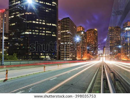 Long exposed trails of headlights and back lights of passing vehicles at sunset along high speed motorway in Sydney CBD at sunset between high-rise towers. - stock photo