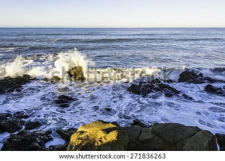 Long exposure at sunrise ocean wave crashing on rocks along the Big Sur coastline near Cambria, CA-California-Central-Coast - stock photo