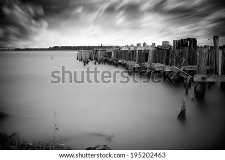Long-exposure, black and white photo of the ruins of an old, abandoned pier reaching into the waters of the St. Lawrence seaway. Taken from Ontario, Canada. New York state, USA is in the distance. - stock photo