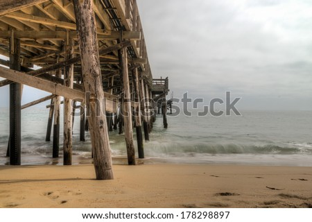Long exposure captures slow moving waves under The Seal Beach Pier in beautiful Seal  Beach, California - stock photo