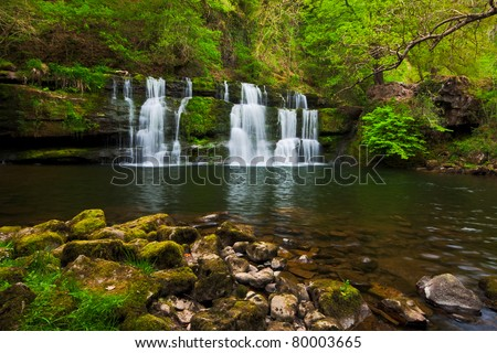 Long exposure image of a waterfall in spring surrounded by lush green foliage. Photo taken at Sgwd y Pannwr, Brecon Beacons national park, Wales. - stock photo