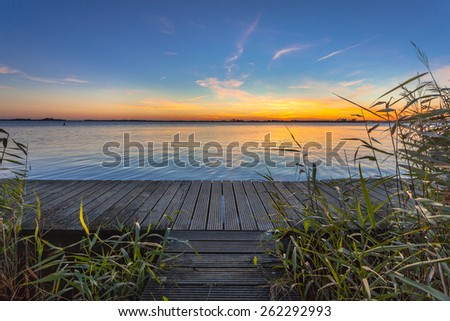 Long exposure image of a wooden walking footbridge as a concept for challenge on lake Schildmeer, Netherlands - stock photo