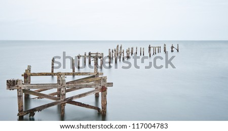 Long exposure image of derelict pier standings in calm smooth ocean - stock photo
