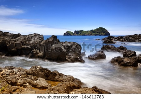 Long exposure image of the rocky coast and the islet of Vila Franca do Campo on Sao Miguel island, Azores - stock photo