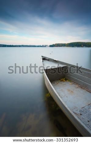 Long exposure landscape of lake shore with moored boats. Lake Krzywe in Olsztyn, Poland. - stock photo