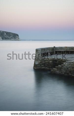 Long exposure landscape of stone jetty in calm seas - stock photo
