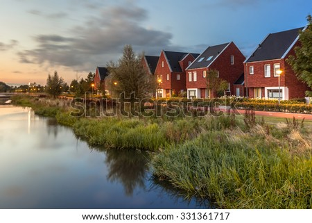 Long exposure night shot of a Street with modern ecological middle class family houses with eco friendly river bank in Veenendaal city, Netherlands. - stock photo