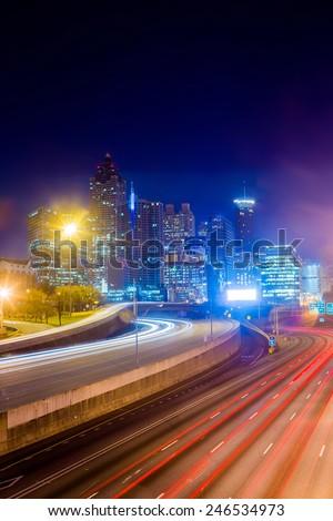long exposure night shot of i-75 and atlanta skyline - stock photo