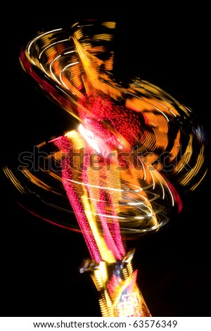 Long exposure of a funfair ride at night - stock photo