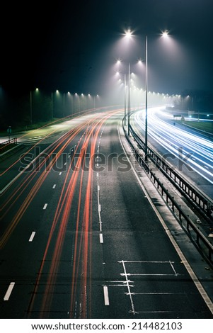 Long exposure of a UK motorway at night time with traffic trails illustrating cars driving on the left. - stock photo